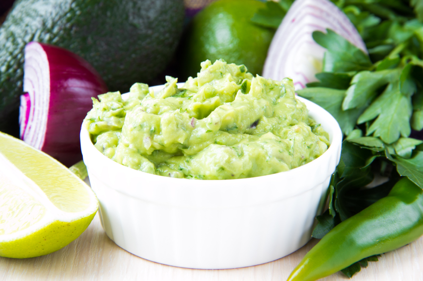 Green Mexican guacamole dip with avocado, lime, parsley and red