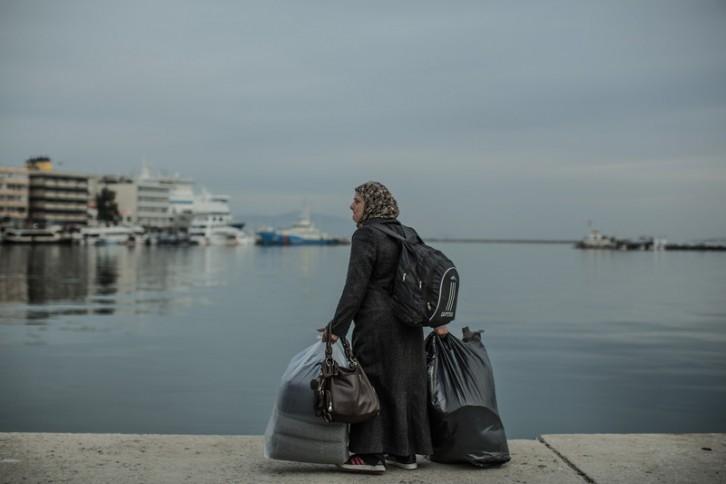 Un grupo de refugiados caminando en dirección al puerto de Lesbos para coger el ferry con dirección Atenas. Les esperan 9 horas de barco hasta llegar al puerto de Pireus. Cada día llegan a las costas de la pequeña isla de Lesvos (Grecia) botes con unas 50 personas refugiadas o migrantes procedentes de Turquía que huyen de la guerra o de la pobreza. Tras pagar a los traficantes cantidades que rondan los 1.000 euros por persona (800 euros si son más de 60 o si hace mal tiempo), arriesgan su vida en un peligroso viaje sin garantías. Con salvavidas de dudosa calidad, sin ninguna nocion de condución, muchas veces de noche y en condiciones meteorológicas adversas. Algunos tienen la suerte de llegar a playas donde les esperan grupos de voluntarios de toda Europa, otros llegan a acantilados inóspitos y solitarios. Más de 4.000 no lograron llegar a la costa en 2015. (c) Pablo Tosco / Oxfam Intermón