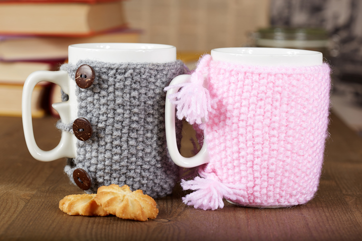 Couple of tea cups with knitted covers and biscuits